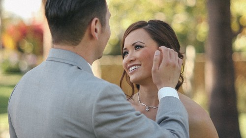 Groom brushes bak brides hair