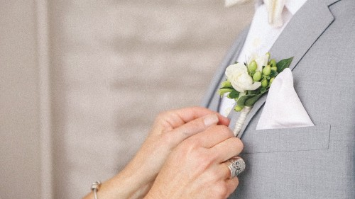 Bride pins on Groom's flower