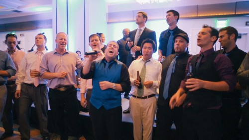 Groom sings with acapella group at wedding