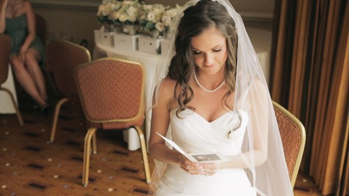 Bride reading letter from groom before wedding ceremony.