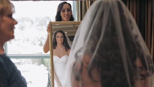 Bride checks makeup in mirror