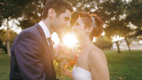 Bride and groom kiss in sunset