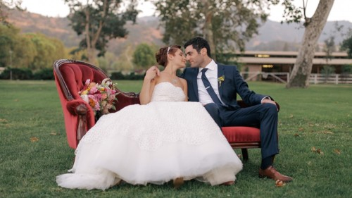 Bride and groom on couch outside