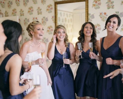 Bride and bridesmaids laughing toast Darlington house