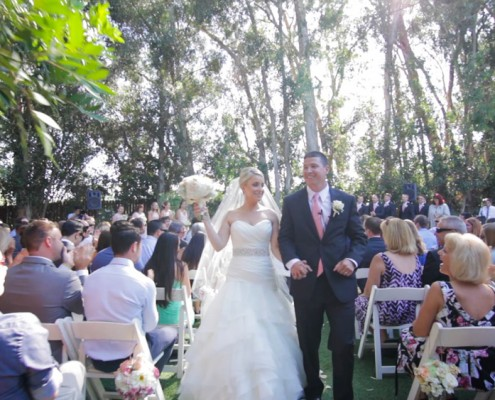 Bride and groom walk down the ailse at Twin Oaks Garden Estate