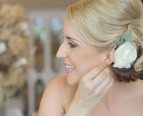 Bride putting in ear ring in San Diego Wedding Video at Twin Oaks Gardens and Estate