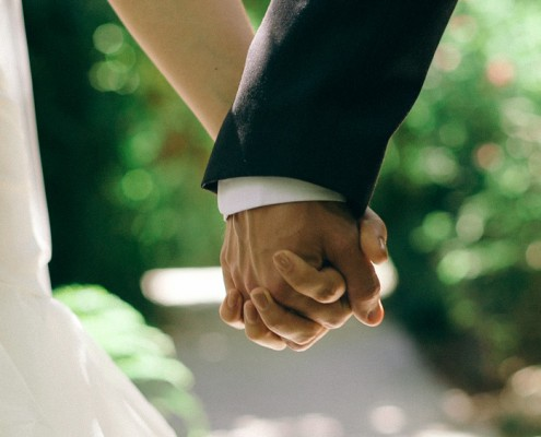 bride and groom hold hands at wedding video