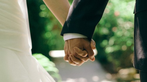 close up of bride and groom holding hands