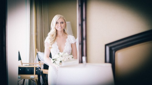 Bride looking in mirror before ceremony.