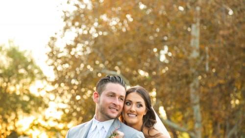 Bride and groom backlit at sunset at Lake Oak Meadows Wedding