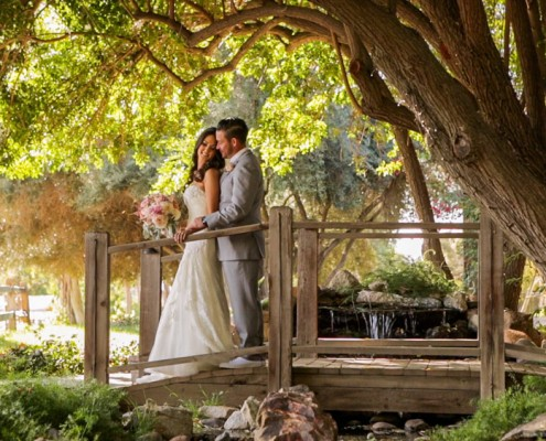 Bride and groom on bridge at Lake Oak Meadows in Temecula wedding video.
