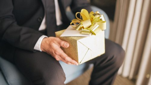 Groom holds gift before wedding