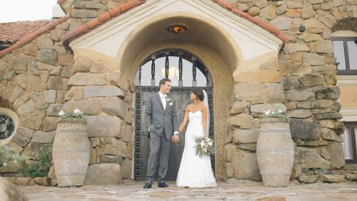 Bride and groom in front of door at Mt. Woodson Castle.