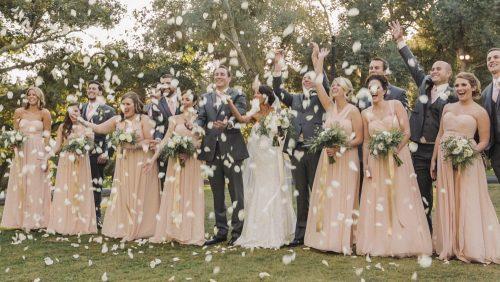 Bridal party throw flower petals at Mt Woodson Castle