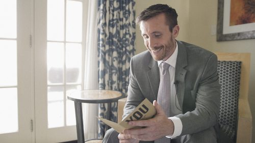Groom reads card before wedding