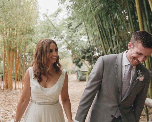 Bride and groom walk near bamboo