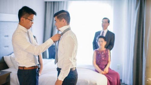 bestman helps with grooms tie