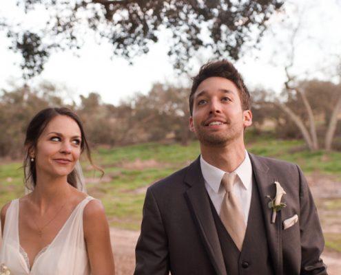 Bride and groom walk under oaks at Mt. Woodson Castle