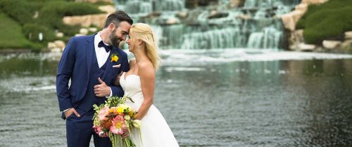 Bride and groom in front of waterfall at crossings at carlsbad wedding