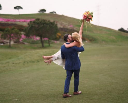 Crossings at Carlsbad wedding bride hold bouquet in the air on golf course