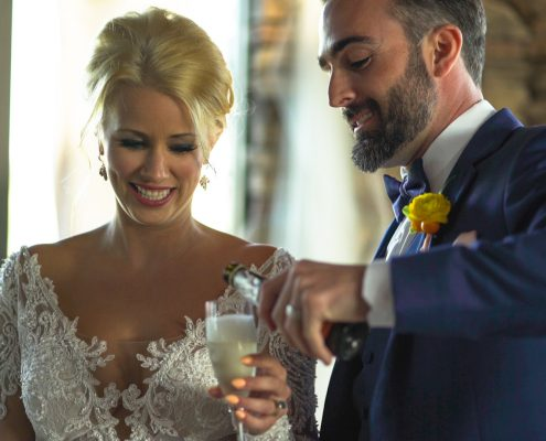 Groom pours champagne for bride
