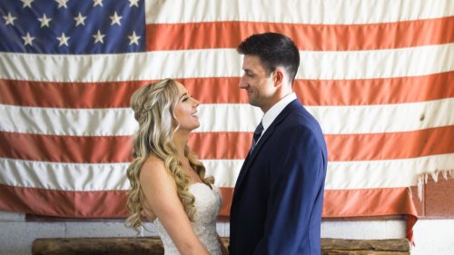 bride and groom in front of american flag